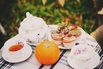 Tea in cups and teapot, cupcakes and pumpkin on the table - бесплатный image #136203