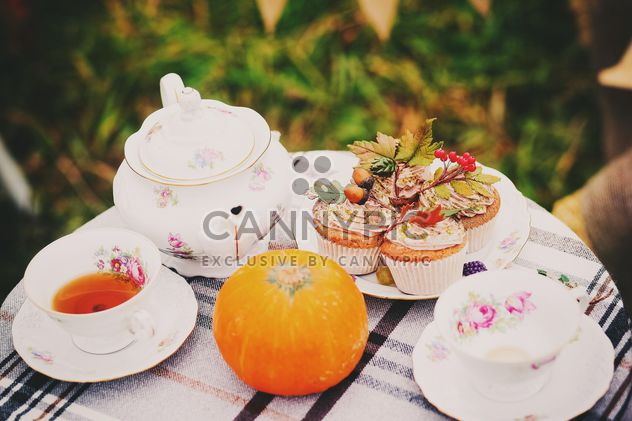 Tea in cups and teapot, cupcakes and pumpkin on the table - Free image #136203