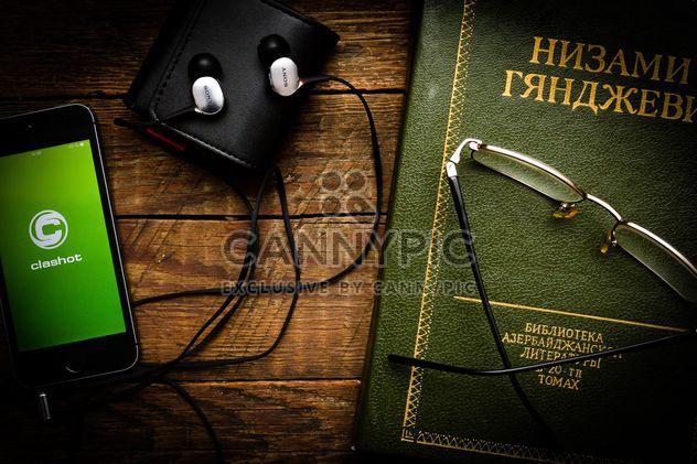 Smartphone con auriculares, libro y gafas - image #182833 gratis