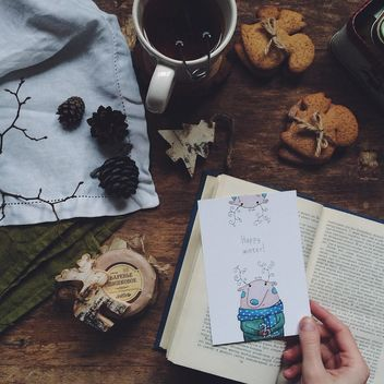 Cup of tea, cookies, open book and postcard in hand - image #183803 gratis