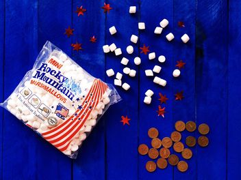 American marshmallows and coins on blue wooden background - image #183833 gratis