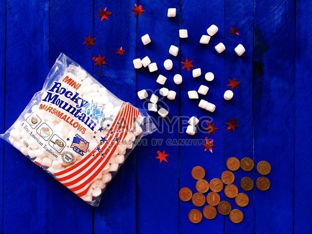 American marshmallows and coins on blue wooden background - Free image #183833