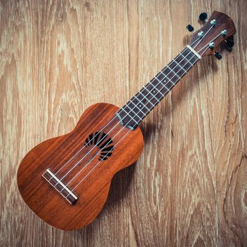 Ukulele on wooden background - image #187023 gratis