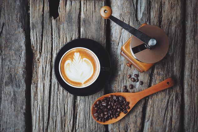 Latte art, coffee grinder and spoon with coffee beans on wooden background - бесплатный image #187093