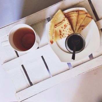Pancakes with jam and cup of tea - бесплатный image #198493
