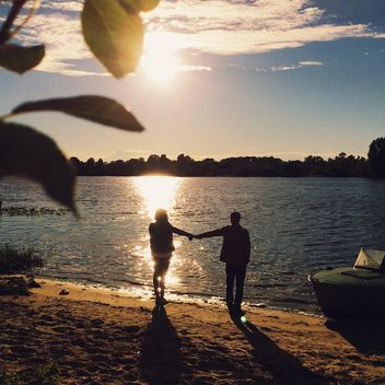 Girl and boy holding hands on the shore of the lake - бесплатный image #271713