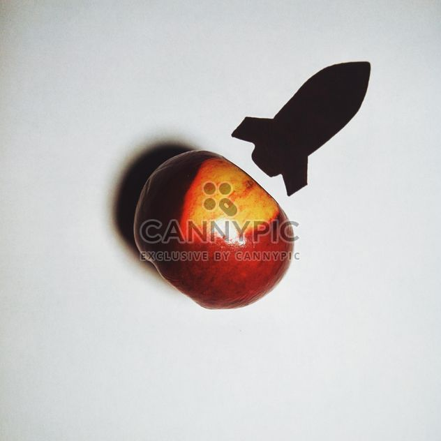 Apple and silhouette of a rocket on white background - Free image #272233
