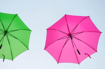 Green and pink umbrellas hanging - image #273063 gratis