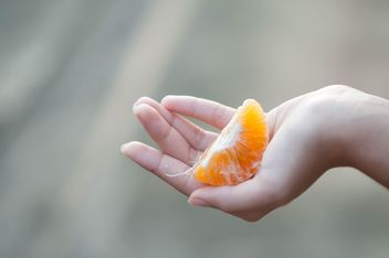 peeled tangerine in hand - Free image #301973