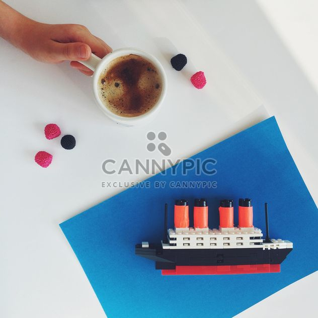 Cup of coffee and toy ship on white abckground - бесплатный image #329163