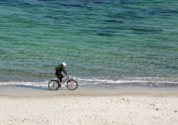 Woman riding a bicycle down the beach - бесплатный image #330323