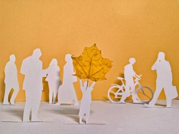 papercut people and yellow maple leaf - бесплатный image #330353