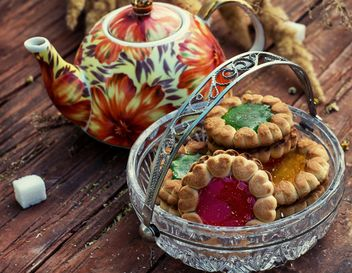 Teapot and cookies on wooden table - бесплатный image #330653