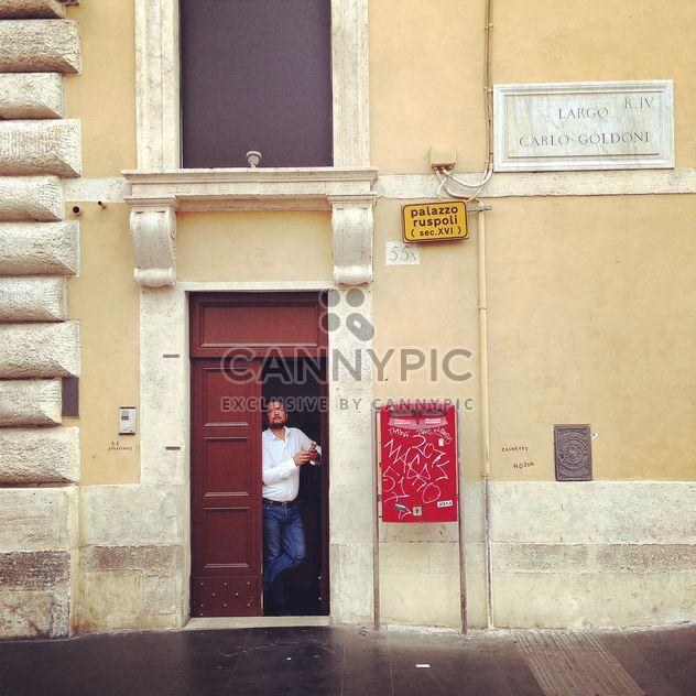 Hombre de pie en la puerta de casa en la calle - image #331633 gratis