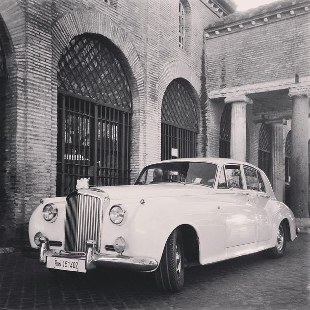 White Bentley near old brick building, black and white - image #331833 gratis