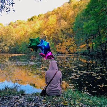 woman siiting on a river bank with colourful baloons - image #332833 gratis