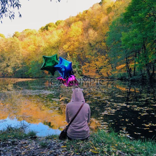 woman siiting on a river bank with colourful baloons - Free image #332833