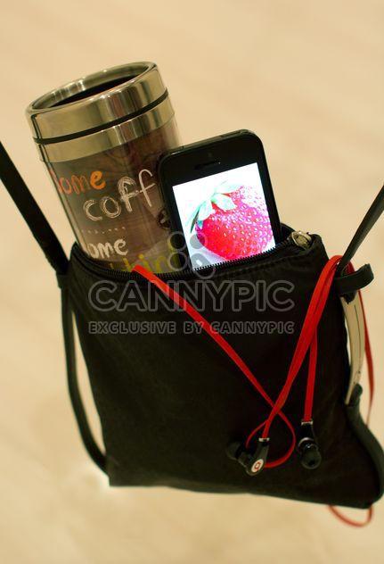 Taza de café y smartphone en bolso - image #337903 gratis