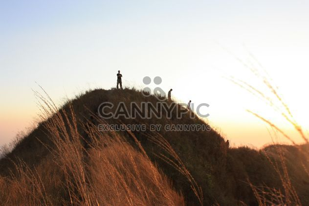 People on rock at sunset - Free image #338493