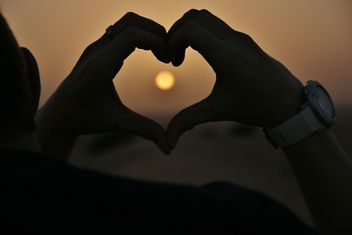 Hands in shape of heart at sunset - image #338513 gratis