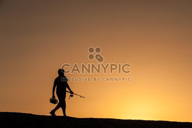 Silhouette of fisherman at sunset - Free image #338523