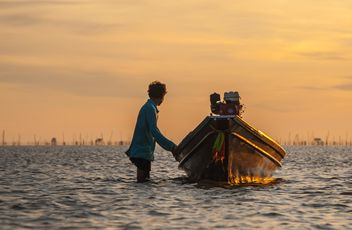 Fisherman with fishing boat at sunset - Free image #338573
