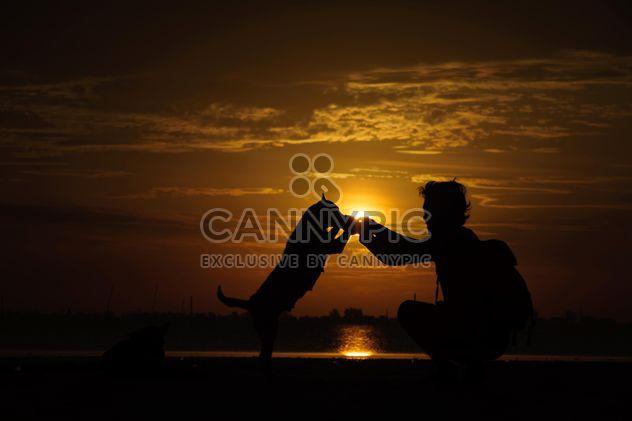 Homme et le chien au coucher du soleil - image gratuit #338593