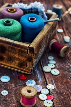 Colored buttons and sewing thread in wooden box on the table - бесплатный image #342903