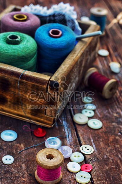 Colored buttons and sewing thread in wooden box on the table - Free image #342903