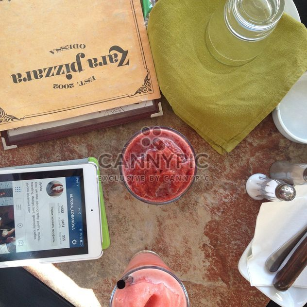 Smoozie em copos ao lado do menu e tablet - Free image #343523