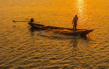 Fisherman in boat on sea at sunset - image #344623 gratis