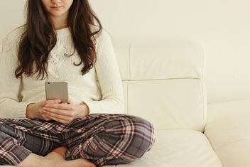 Girl with smartphone sitting on sofa - image #344633 gratis