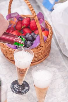 Two glasses of champagne and fruit in basket - бесплатный image #345033