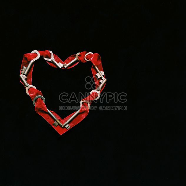 Heart made of keys and ribbons on black background - Free image #345913
