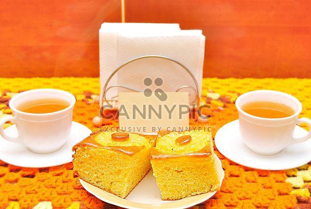 Dos tazas de té y tortas en la mesa - image #346553 gratis