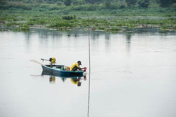 Fisherman in fishing boat on river - image #347283 gratis