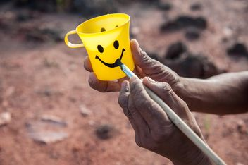 Hands painting smile on yellow cup - image gratuit #347313