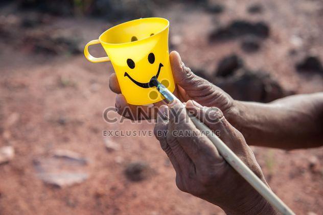 Hände malen Lächeln auf gelbe Tasse - Kostenloses image #347313