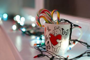 Christmas candies in cup and garlands - image #347823 gratis