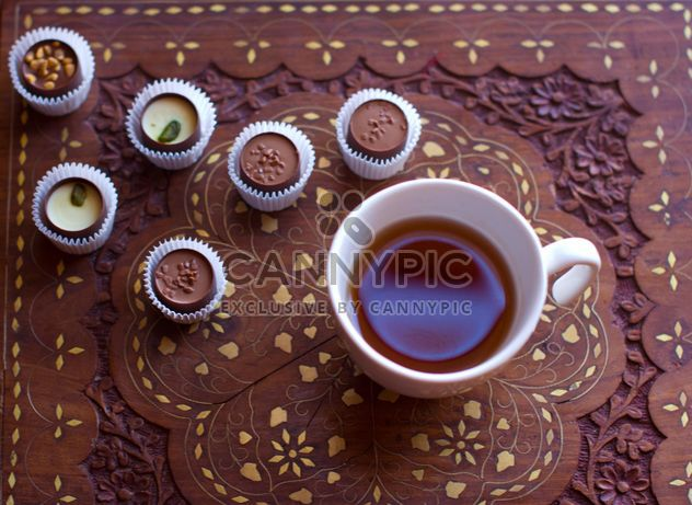 Cup of hot tea and candies on wooden background - Free image #347913