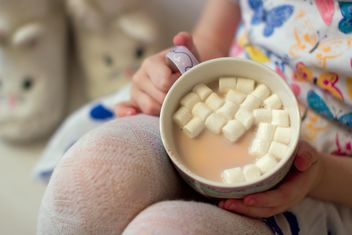 Cup of cocoa with marshmallows in child's hands - бесплатный image #347963