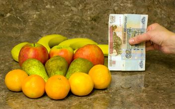 Fresh ripe fruit and money in hand - бесплатный image #348003
