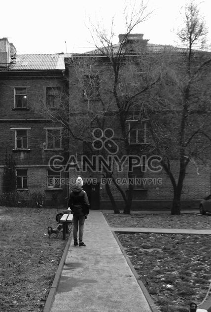 Person in front of house in town, black and white - Free image #348033