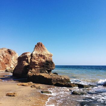 Rocks in sea under blue sky - image #136213 gratis
