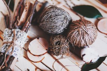 Skeins of wool, cotton and sticks on wooden background - image #136263 gratis