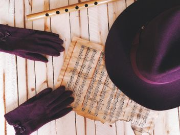 Purple gloves, hat, notes and pipe over wooden background - бесплатный image #136273