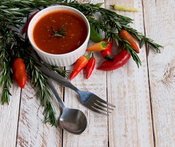 tomato sauce with rosemary and chili peppers on a wooden table - image #183363 gratis