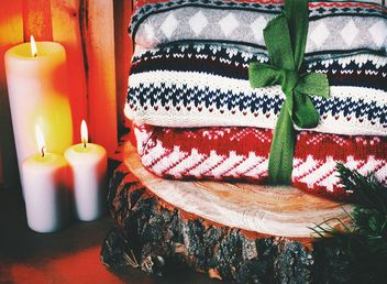 Closeup of warm wool sweaters tied with ribbon on wooden stump - image #183733 gratis