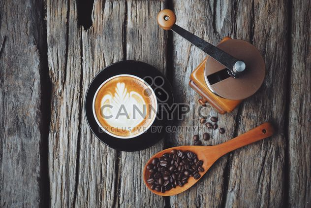 Latte art, coffee grinder and spoon with coffee beans on wooden background - image gratuit #187093