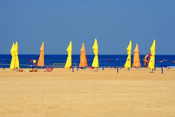 Beach umbrellas on seashore - Free image #187753